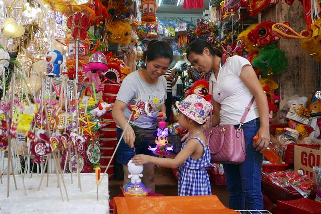 Bé gái được mẹ đưa đi mua đồ chơi Trung thu sớm ở một cửa hàng trên phố Hà Mã.